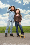Stock photos of two young multi-ethnic girls with inline skates and a skateboard in the park with a blue sky
